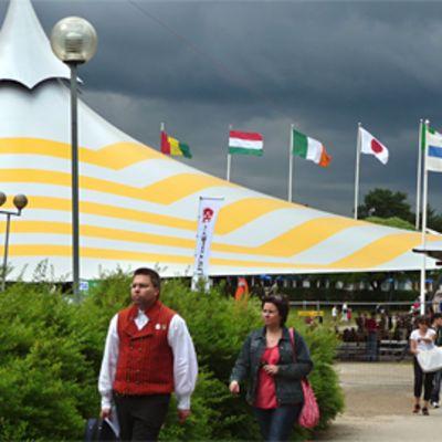 Festivaaliteltta ja liehuvia eri maiden lippuja, joiden taakse on kerääntynyt tummia pilviä.
