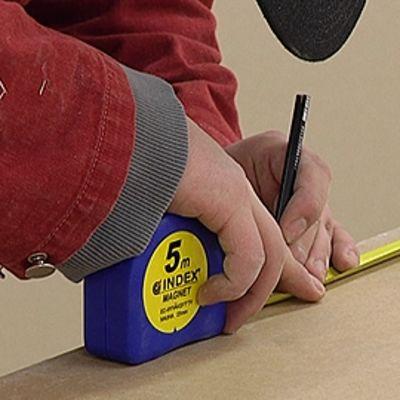 Rakennusmies mittaa levyä mittanauhalla ja tekee merkintää levyyn.