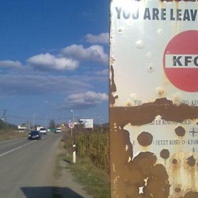 """Kuvassa näkyy maantie ja sen vieressä kyltti, jossa teksti: """"You are leaving Kosovo"""" sekä KFORin teksti."""