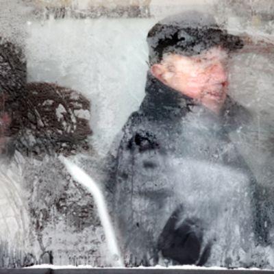 Matkustaja katsoo ulos raitiovaunun jäätyneestä ikkunasta Varsovassa.