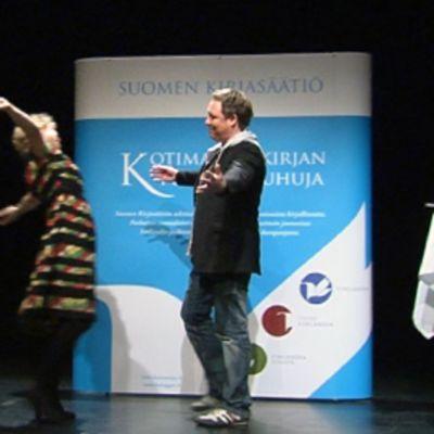Minna Joenniemi onnittelee Mikko Rimmistä Vanha ylioppilastalon lavalla.