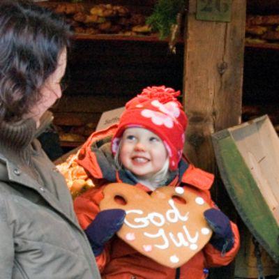 """Punapipoinen pikkutyttö pitelee isoa piparkakkua, jossa teksti """"God Jul"""". Toisella puolella äiti, toisella pullaa syövä isä. Takana myyntikojun puupilari."""