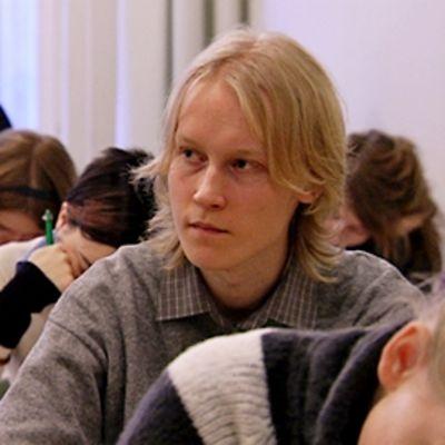 Risto Tiihonen kuuntelee luennoitsijaa yliopiston luennolla.