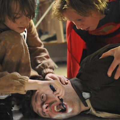 Kaksi lasta harjaa maassa makaavan miehen hampaita hammasharjalla.