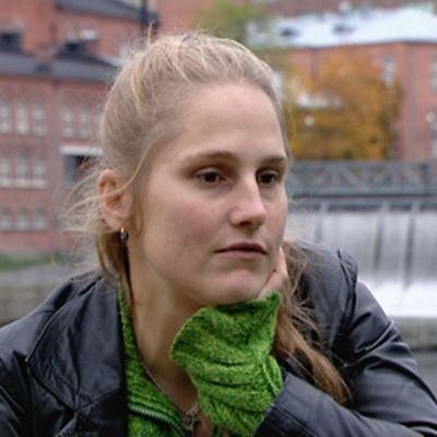 Alexandra Salmela istuu puistonpenkillä, takanaan tamperelelainen koskimaisema.