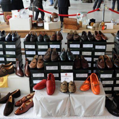 Kymmenittäin kenkiä myynnissä. Laatikkopinoja.