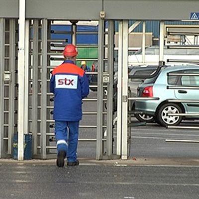 """Stx:n työntekijä kävelee portista ulos kypärä ja sinipunainen työasu päällään. Selkämyksessä lukee """"STX""""."""