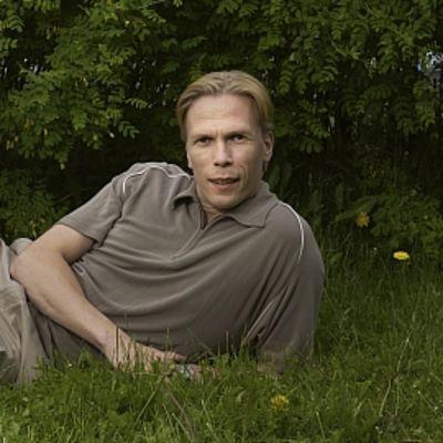 Näyttelijä Harri Hinkkalojuu ruohikolla.