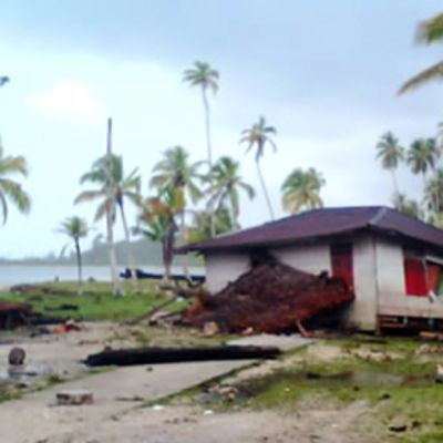 Palmuja ja tuhoutunut talo meren rannalla.