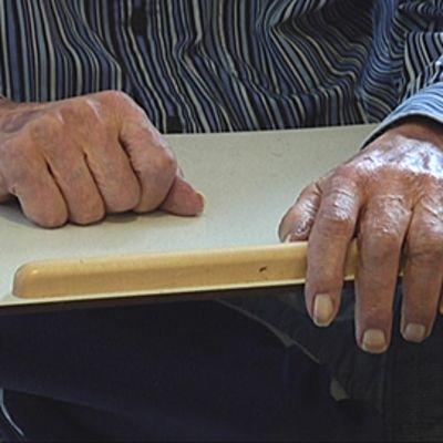 Vanhuksen kädet pöydällä.