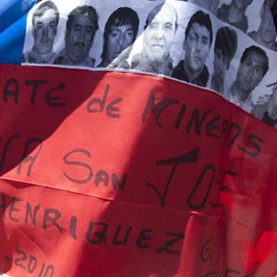Chilen lippuun on liimattu 33 kaivosmiehen kasvokuvat. Lipun punaiselle alueelle on kirjoitettu: 'Miners rescue, San Jose Mine, Jose Rodriguez'.