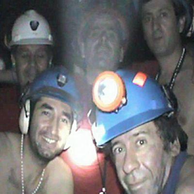 Viisi kaivosmiehestä seisoo takana ja kaksi istuu edessä yhteiskuvassa kaivoksen pimeydessä, jota valaisevat vain miesten otsalamput.