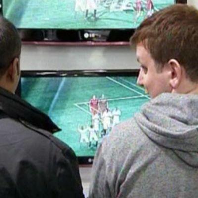 Kaksi nuorta miestä kokeilee FIFA 11 -jalkapallopeliä liikkeessä.