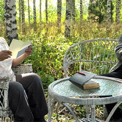 Leila (Karina Hazard) lukee kirjettä pappi Jaakobille (Heikki Nousiainen) puutarhapöydän ääressä koivikossa.