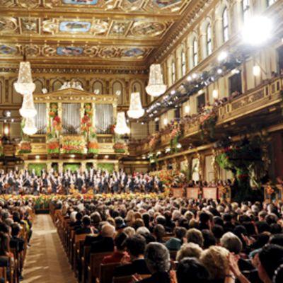 Kullalla ja maalauksin koristettu konserttisali. Kristallikruunuja ja paljon yleisöä.