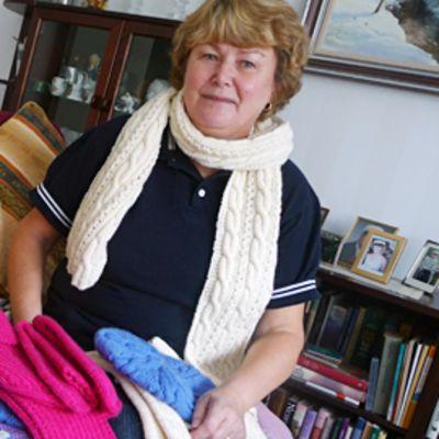 Kuvassa Seija Kaustinen sohvallaan neuletöiden kanssa