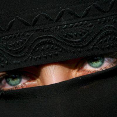 Nainen pukeutuneena kasvot peittävään Niqabiin. Naisen silmät näkyvät kankaiden välistä.