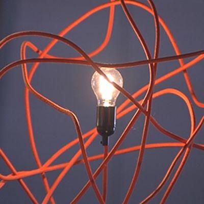 Hehkulamppu, jonka varjostimena punaisesta rautalangasta tehty vyyhti.