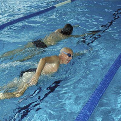 Kaksi ihmistä kroolaamassa uimahallissa.