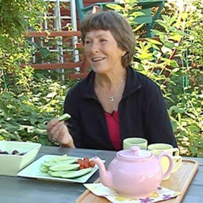 Kuvassa Liisa Torikka puutarhapöydän ja puutarhan antimien ääressä