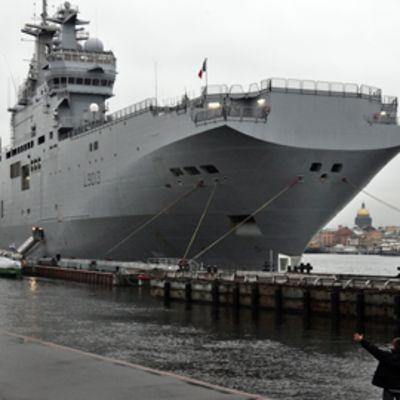 Etualalla oleva mies heiluttaa käsiään jättimäisen sotalaivan saapuessa satamaan.