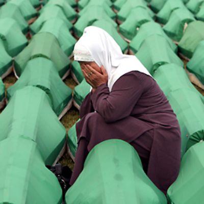 Sureva musliminainen arkkurivistön välissä. Hän on peittänyt kasvonsa käsillään.