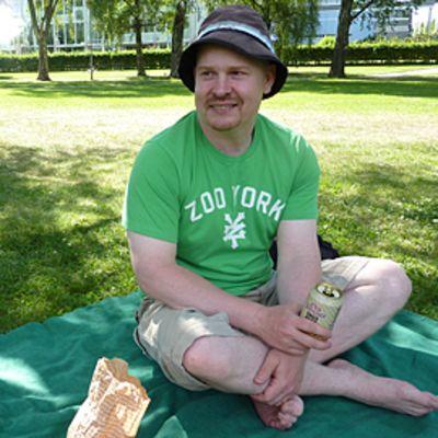 Matti Huhta istuu viltillä puistossa.