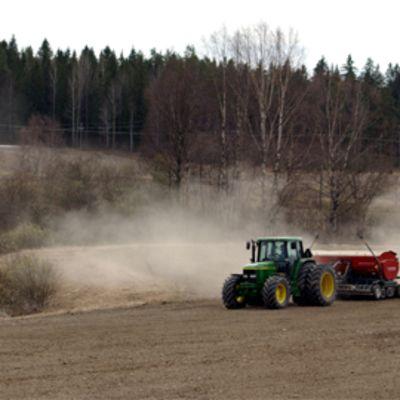 Traktori ja kylvökone pellolla kevätkylvön aikaan.