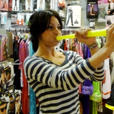 Jenni Karjalainen näyttää, miten vuvuzela-torvesta saa ääntä.