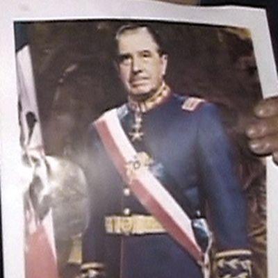 Nainen pitää käsissään Augusto Pinochetin kuvaa ja kynttilää.