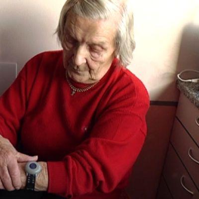 Ikäihminen turvapuhelimen hälytysranneke kädessään