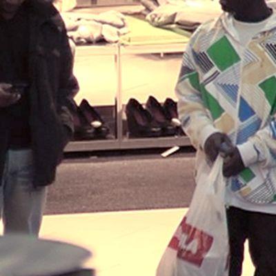 Kaksi nuorta miestä ostoskeskuksessa, toisella kännykkä, toisella ostoskassi.