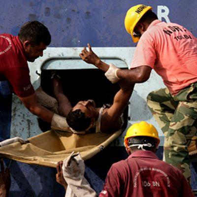 Pelastustyöntekijät auttoivat onnettomuuden uhria pois turmajunasta.