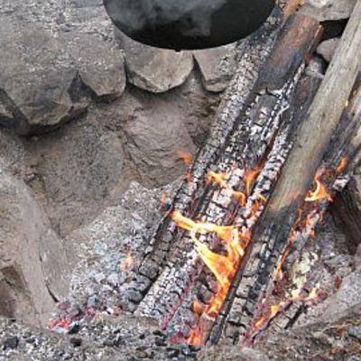 Kivillä vuoratussa rosvopaistihaudassa poltetaan nuotiota
