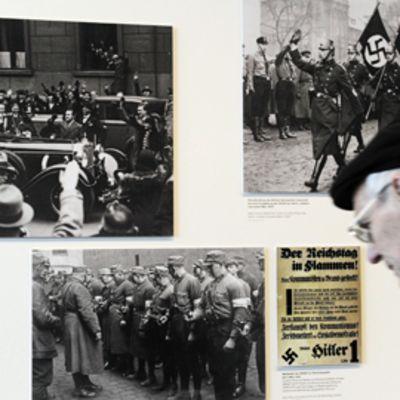 Vanha mies tutkii kuvia natsiaiheisessa näyttelyssä Berliinissä.