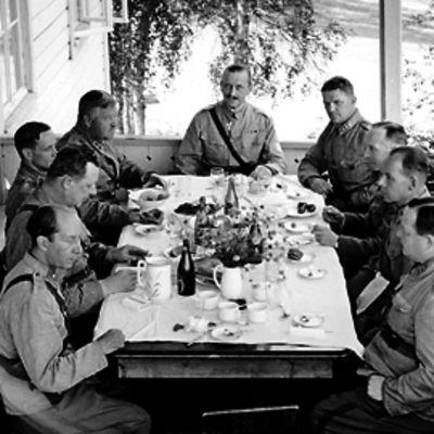 Eversti Aaro Pajarin tarjosi lounaan pappilan verannalla. Pöytäseurueessa oli armeijakunnan johtoa ja muita upseereita Mannerheimin ohella. Seinällä nojailee piika.