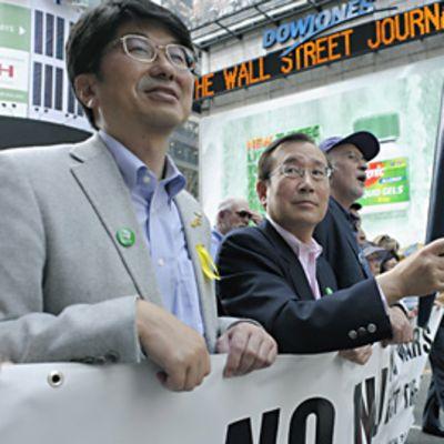 Hiroshiman pormestari kantaa soihtua mielenosoitusmarssin kärjessä. Taustalla New Yorkin mainoksia ja mainosledivaloja.