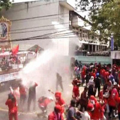 Sotilaat ampuvat mielenosoittajia vesitykillä armeijan tukikohdan ulkopuolella Bangkokissa.