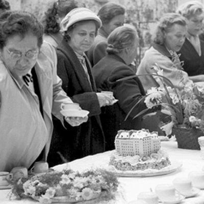 Asukkaita pihalla suuren pitopöydän äärellä. Ottavat pöydäastä kahvia. Pöydässä kivitaloa esittävä täytekakku sekä kukkia. Mustavalkokuva vuodelta 1953.