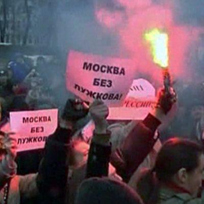 Joukko mielenosoittajia joista yhdellä soihtu kädessä