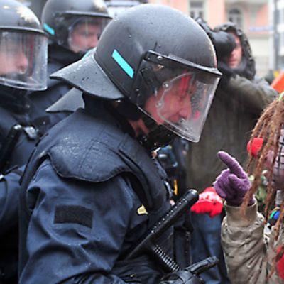 Klovniksi pukeutunut mielenosittaja keskustelee mellakkavarusteisen poliisin kanssa Münchenissä helmikuussa 2010