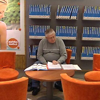 Mies selailee esitteitä matkatoimistossa
