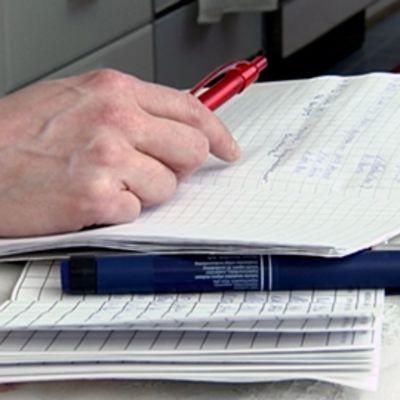 Kodinhoitaja kirjoittaa terveystietoja ruutuvihkoon vanhuksen kotona.