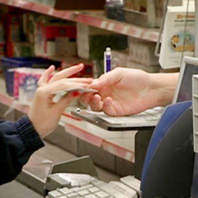 Asiakas maksaa kortilla kaupan kassalla.