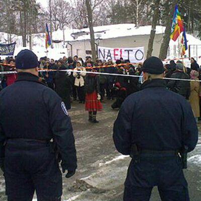 Natoa vastustavia mielenosoittajia lippuineen ja banderolleineen. Etualalla poliiseja rivissä.