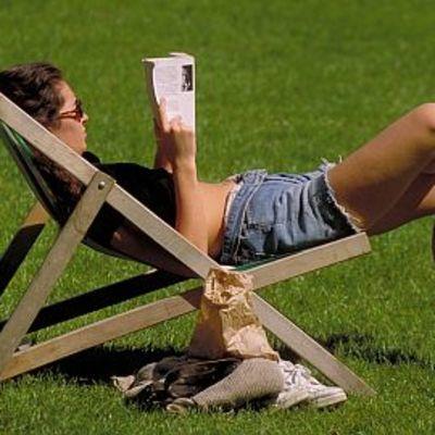 nainen lukee kirjaa aurinkotuolissa