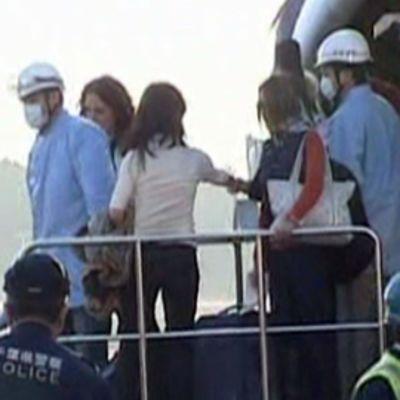 Lento-onnettomuuden uhreja kannetaan koneesta pois.