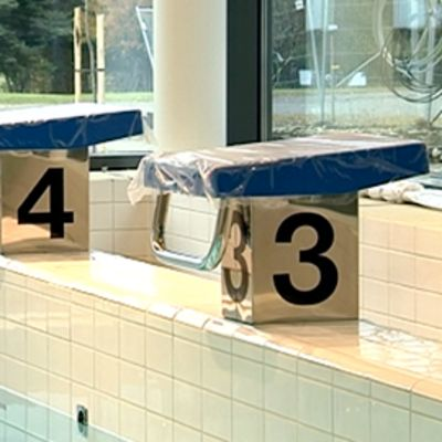 Numeroidut lähtöpaikat uima-altaan reunalla.