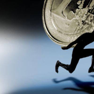 Piirroshahmo kantaa selässään euron kolikkoa.