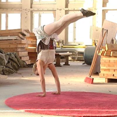 Sirkustaiteilija Kristiina Janhunen seisoo käsillään Suvilahden Kojehuoneen lattialla.